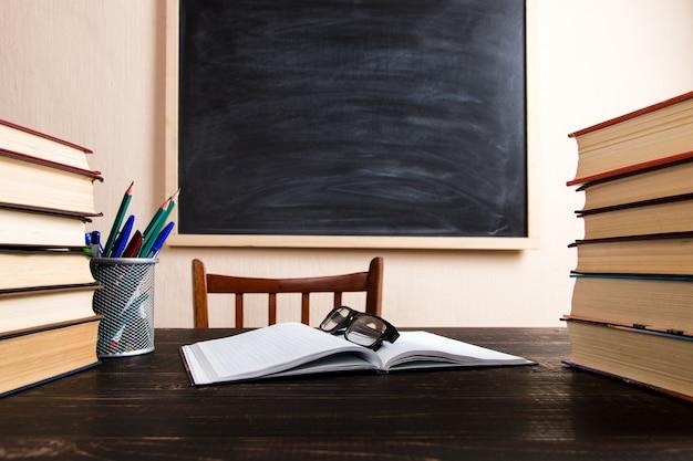 Livros, canetas, lápis e óculos em uma mesa de madeira, contra um quadro de giz.