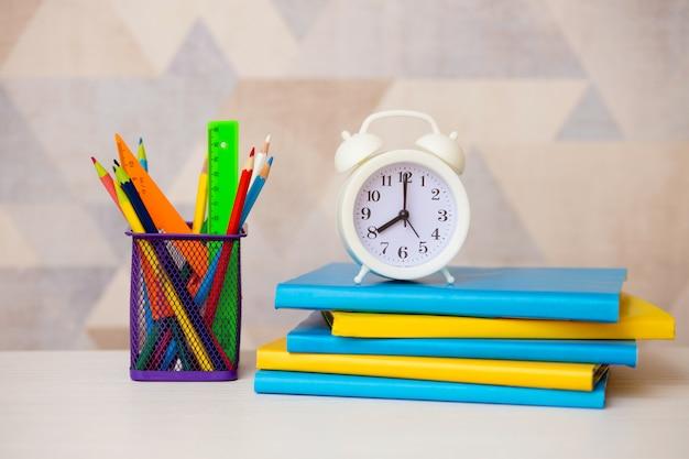 Livros coloridos brilhantes, despertador e lápis de cor sobre um fundo claro. de volta à escola.