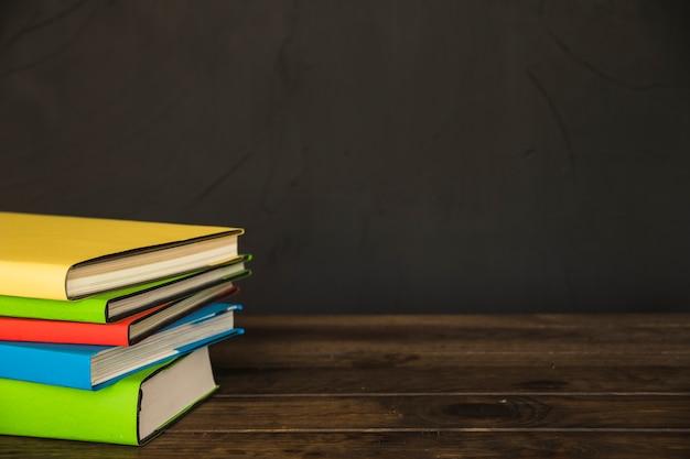 Livros coloridos na mesa de madeira