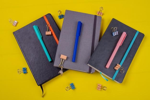 Livros com canetas hidrográficas e clipes de papel.