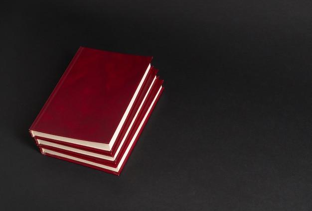 Livros com capa vermelha em fundo preto, isolados. de volta à escola