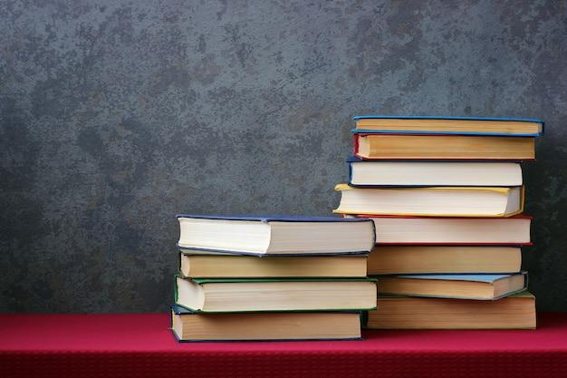 Livros com capas coloridas na mesa com uma toalha de mesa vermelha