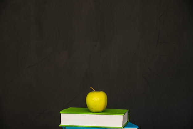 Livros com maçã verde no topo