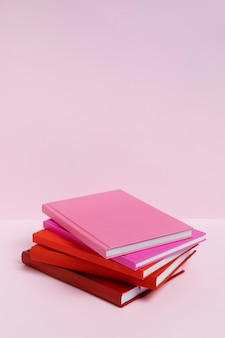 Livros de ângulo alto com fundo rosa