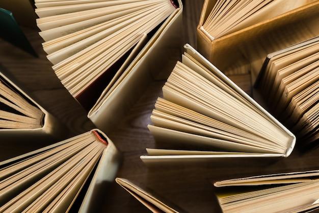 Livros de capa dura velhos e usados, livros de texto vistos de cima no chão de madeira.