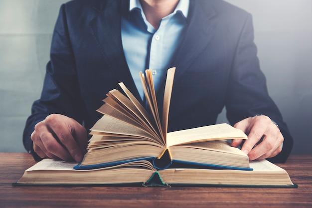 Livros de mão de homem na mesa de madeira