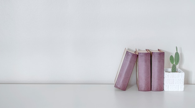 Livros de maquete e planta de casa na mesa superior de madeira branca com parede branca, copie o espaço para a exposição do produto.