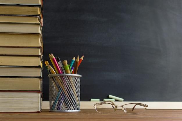 Livros de professor de óculos e um stand com lápis sobre a mesa, no fundo de um quadro negro com giz