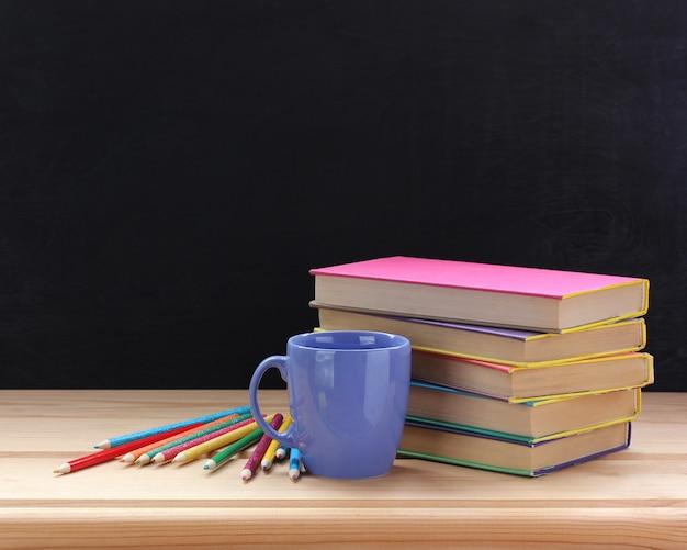 Livros didáticos em capas coloridas e lápis de cor