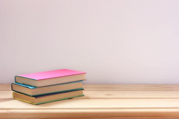 Livros didáticos em capas de cor em uma mesa de madeira