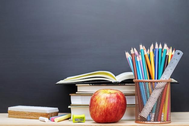 Livros do professor de óculos e um suporte com lápis sobre a mesa, no fundo de uma lousa com giz