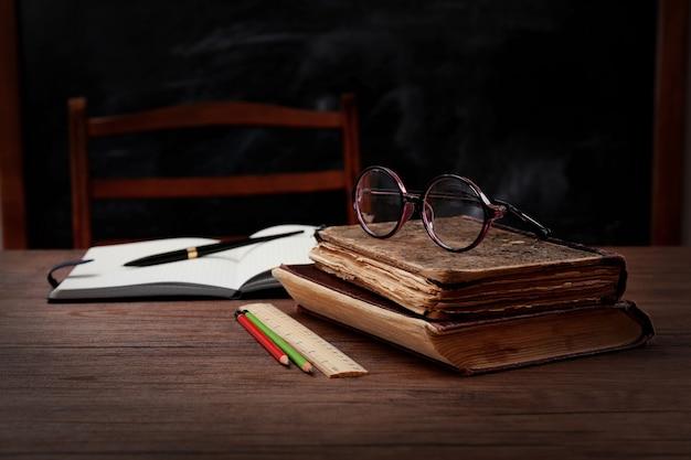 Livros e acessórios escolares na mesa de madeira