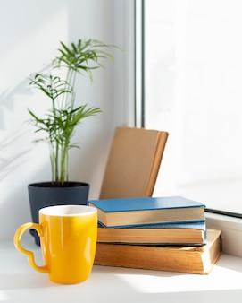 Livros e arranjo de xícaras