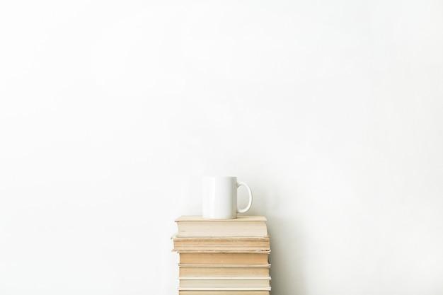 Livros e caneca de café na superfície branca