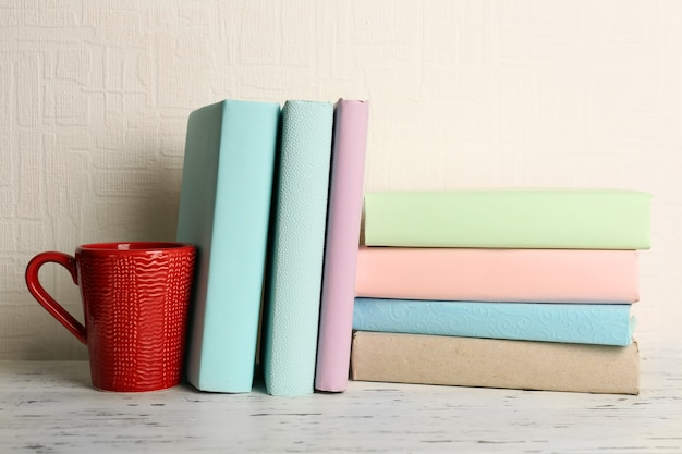 Livros e copo na prateleira de madeira no espaço do papel de parede