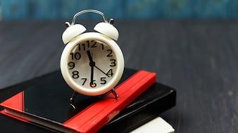 Livros e despertador relógio branco sobre um fundo azul de madeira