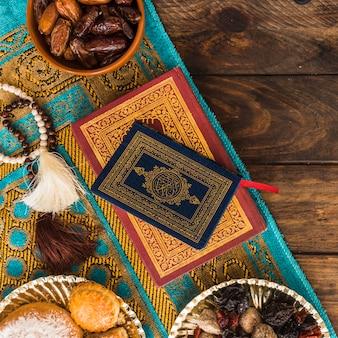 Livros e miçangas perto de doces árabes