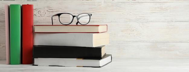 Livros e óculos contra o fundo de madeira rústico, espaço para texto