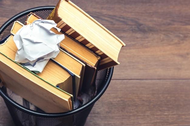 Livros e papel amassado na lixeira