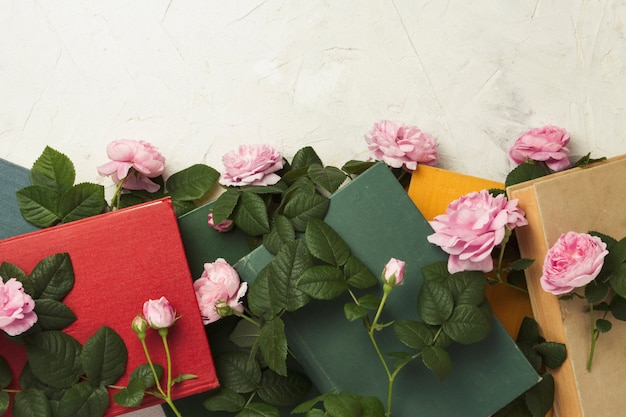 Livros e rosas em uma superfície de pedra clara.