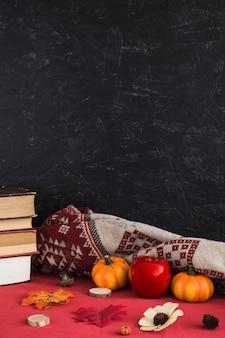 Livros e símbolos de outono perto de cobertor