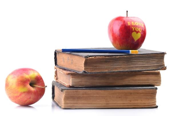 Livros e uma maçã em um fundo branco