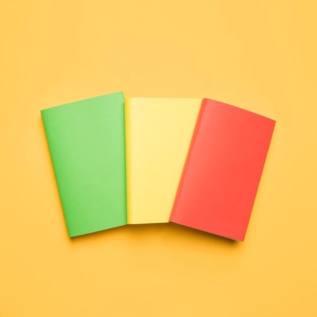 Livros em branco coloridos sobre fundo amarelo