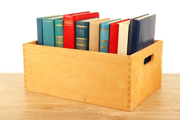 Livros em caixa de madeira isolados no branco