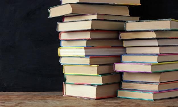 Livros em pilhas na mesa de uma lousa de escola.