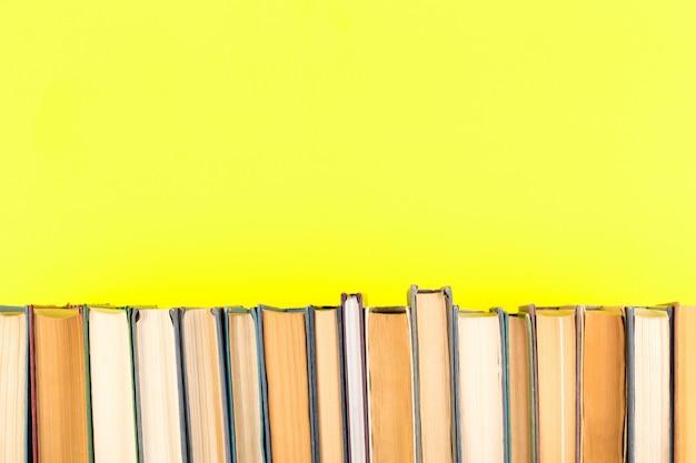 Livros em uma fileira contra o fundo amarelo.