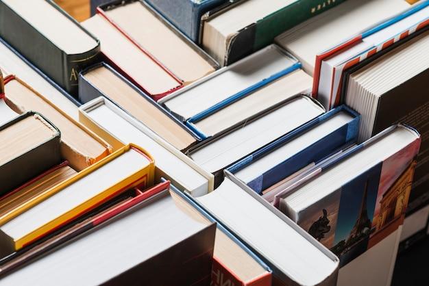 Livros empilhados aleatoriamente na prateleira