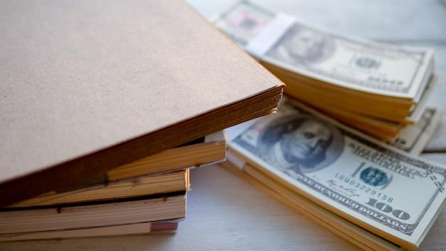 Livros empilhados com dinheiro dólar colocados na mesa