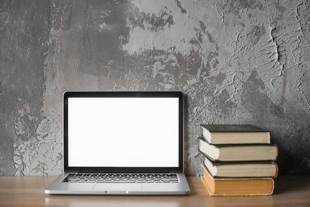 Livros empilhados e laptop com tela branca em branco na superfície de madeira
