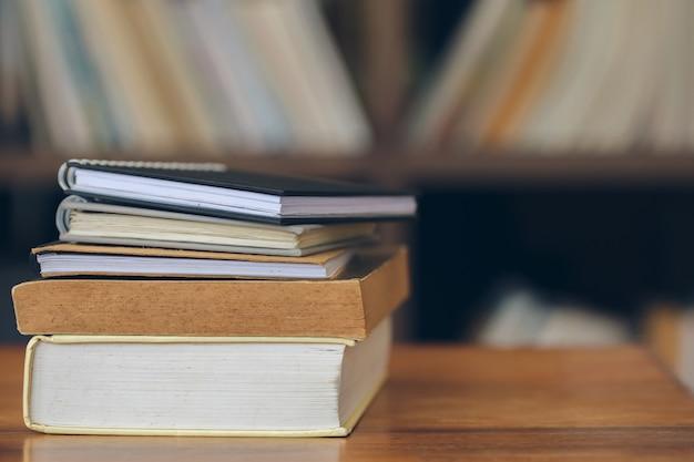 Livros empilhados sobre a mesa de madeira velha na biblioteca.