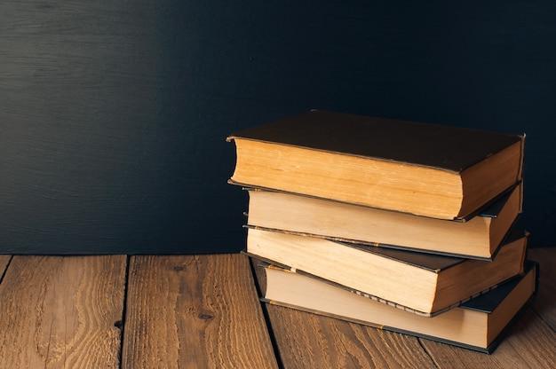Livros empilhados sobre uma mesa de madeira em estilo rústico no fundo de um quadro negro escolar.