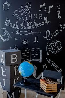 Livros escolares e mesa escolar com quadro-negro