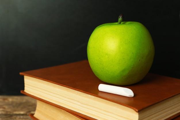 Livros escolares na mesa perto do quadro-negro