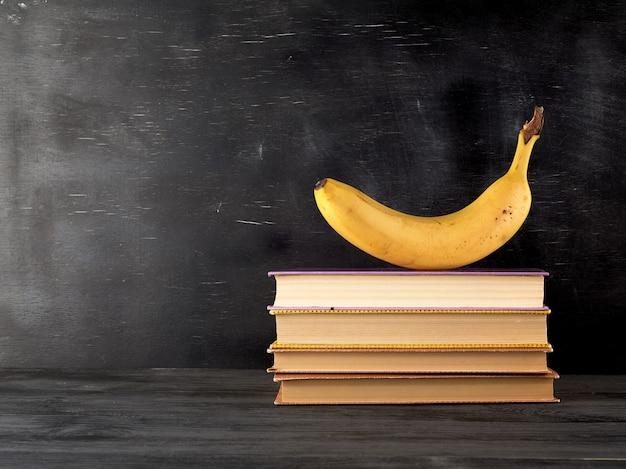 Livros fechados com lençóis amarelos e banana madura