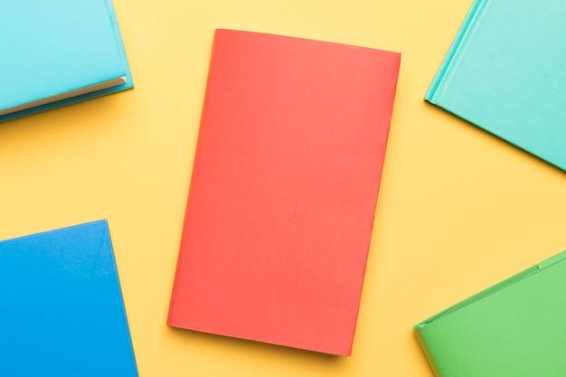 Livros fechados, dispostos na mesa amarela
