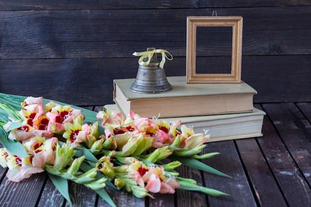 Livros, gladiulos, uma moldura para uma foto e um velho sino