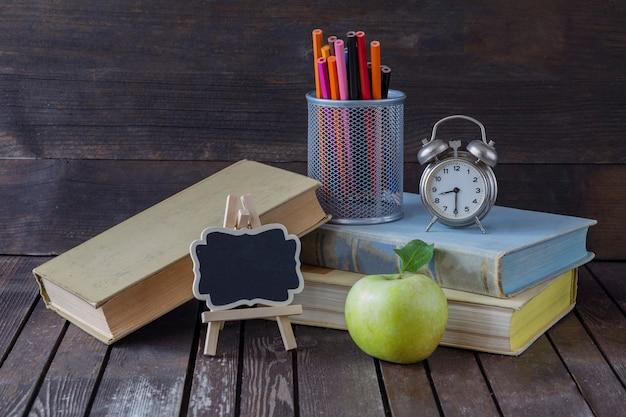 Livros, lápis de cor, despertador, maçã verde e uma placa de escrita
