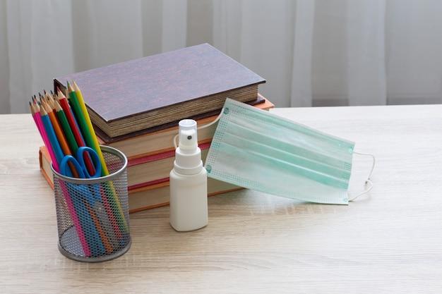 Livros, lápis, protetor facial e desinfetante para as mãos estão sobre a mesa