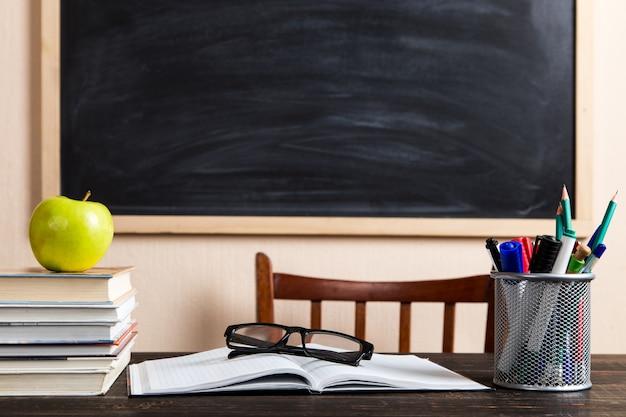 Livros, maçã, canetas, lápis e óculos em uma mesa de madeira, contra um quadro de giz.