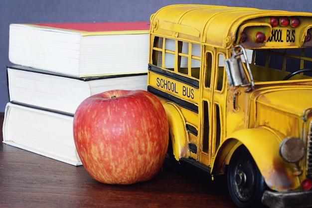 Livros, maçã, giz de cera e ônibus escolar