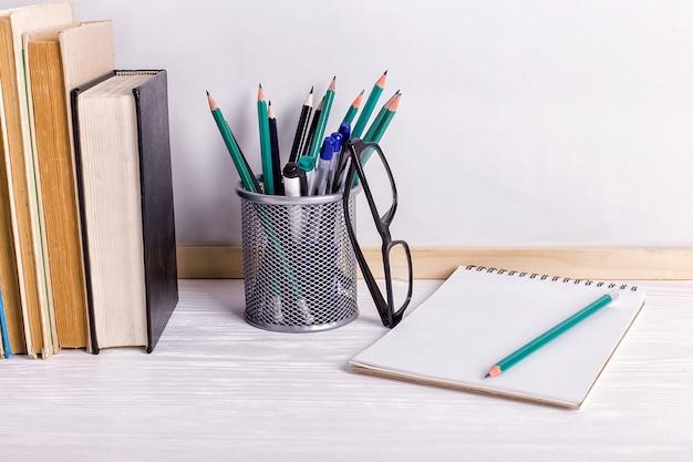 Livros, marcadores, caderno, lápis e óculos na mesa