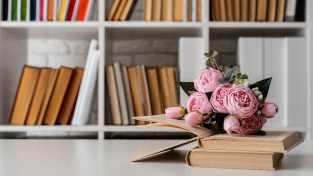 Livros na estante e arranjo de flores