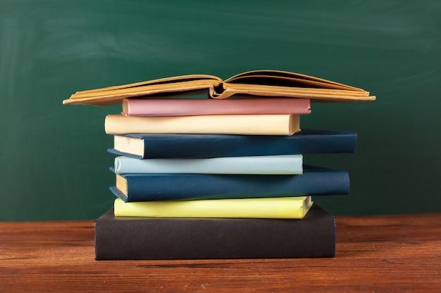 Livros na mesa, fundo de quadro de giz