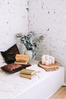 Livros no sofá branco com almofadas em casa aconchegante