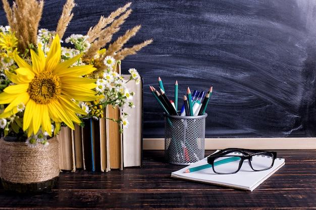 Livros, óculos, marcadores e um buquê de flores em um vaso branco