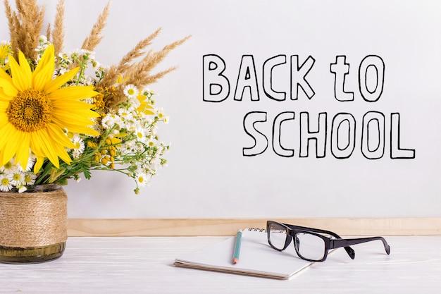 Livros, óculos, marcadores e um buquê de flores em um vaso